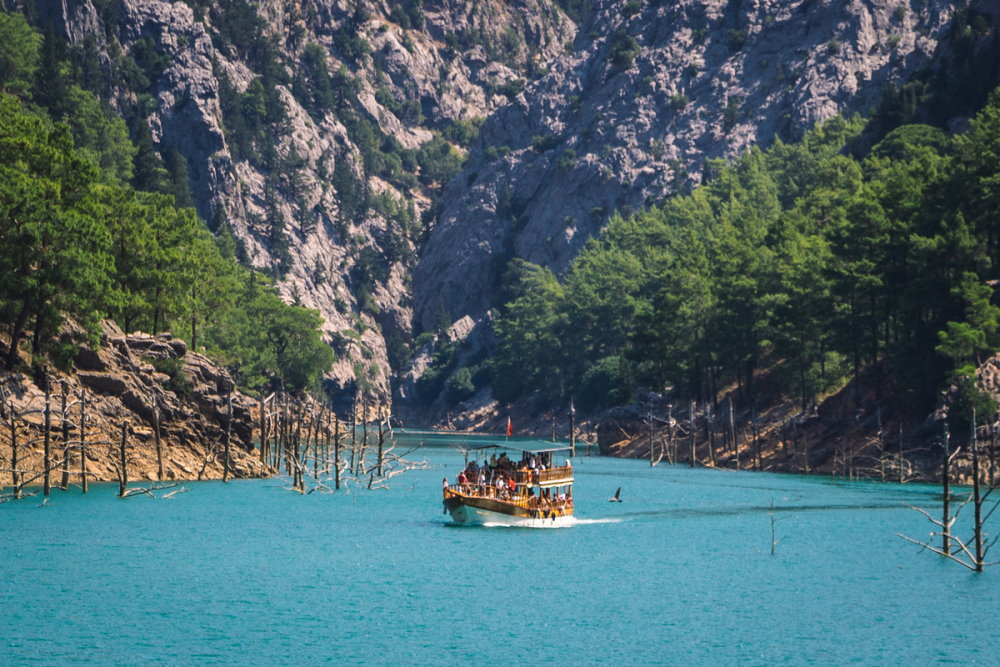 Wooden tourist boat sail in green canyon Alanya in Turkey